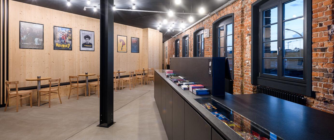 Blick auf den Verkaufstresen und geräumigen Foyerbereich mit unterfahrbaren Tischen, sowie Sitzmöglichkeiten.