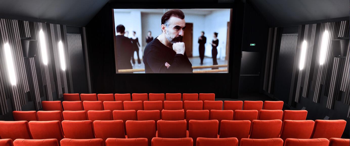 Der große Kino-Saal mit 93 orangeroten Samtsesseln. Auf der Leinwand läuft ein Film mit einem grübelnden Ballett-Lehrer.