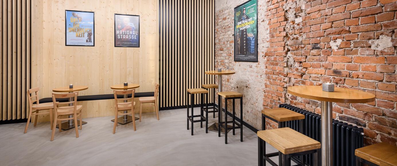 Kino-Foyer mit verschiedenen Sitzmöbeln und Tischen aus hellem Holz